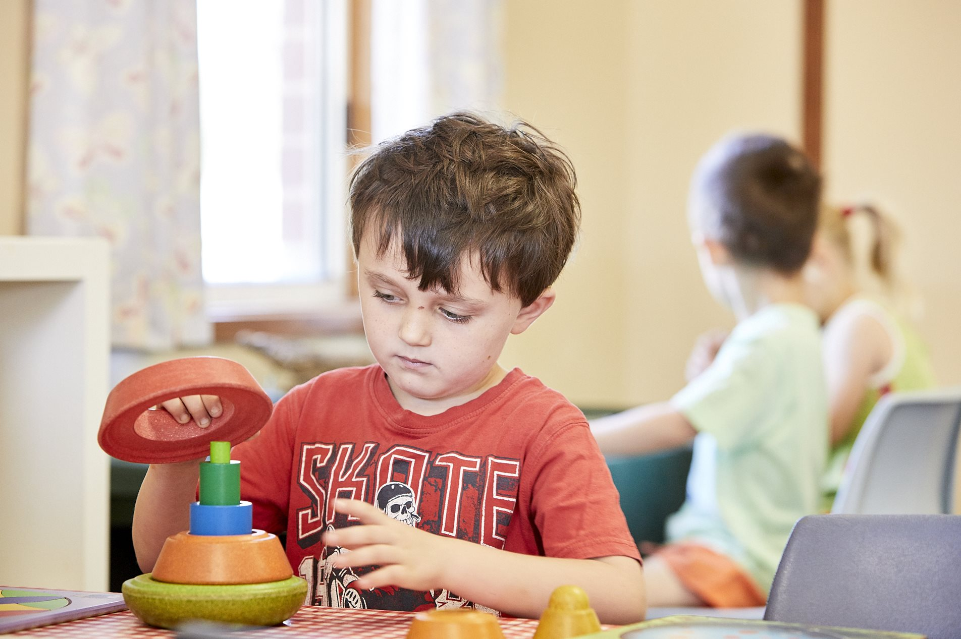 Child concentrating on building blocks in classroom